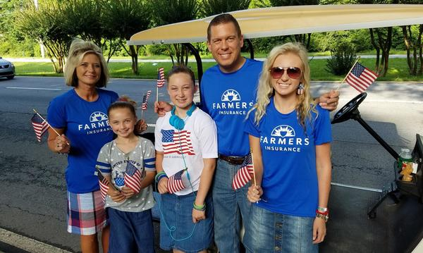 A family of five wearing Farmers Insurance shirts and holding American Flags.