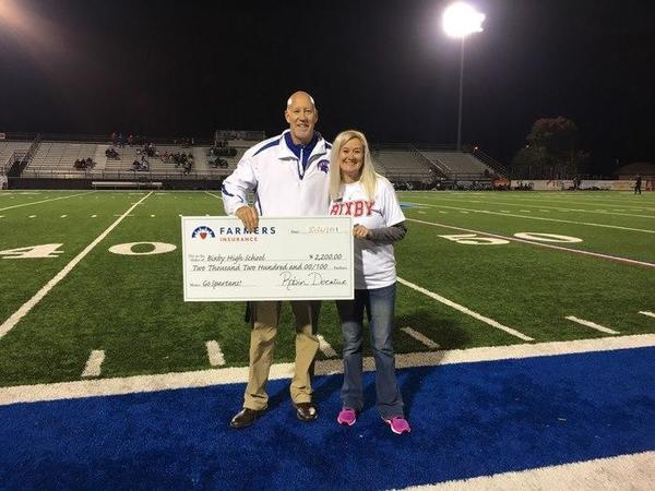 A man and a woman posing with a large check on a football field.