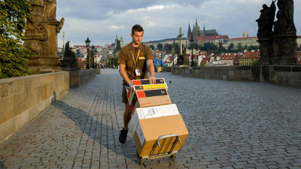 UPS driver transporting international deliveries using dolly