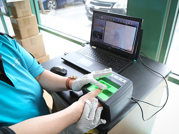A The UPS Store associate scans the fingerprint of a customer's thumb