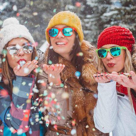 Three friends throwing confetti in the snow
