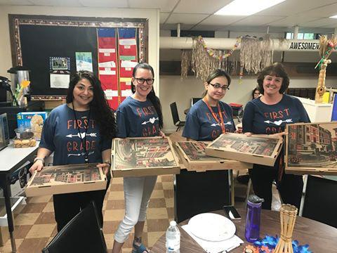 group of women holding pizzas