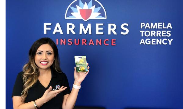 Agent posing in front of blue wall displaying Farmers logo