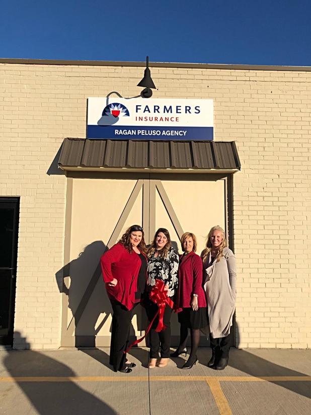 Farmers staff pose in front of ribbon cutting for Farmers Agency