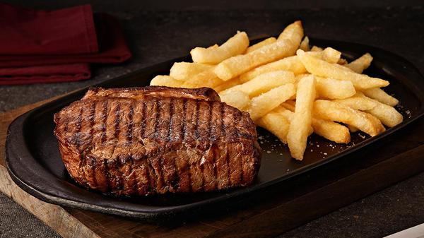 Steak and fries on a black plate