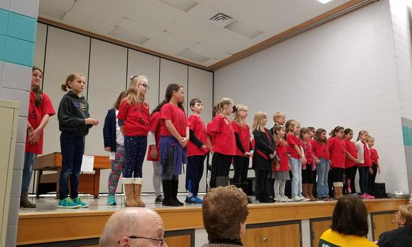 A Group of Children in Red Shirts Performing for the audience