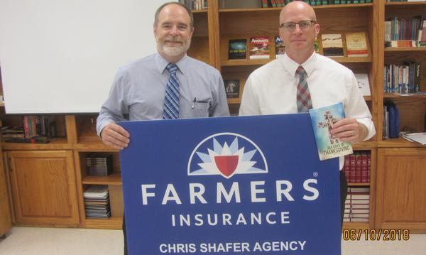 Agent Chris Shafer standing in a classroom with a man holding a sign for Farmers Insurance Chris Shafer Agency.