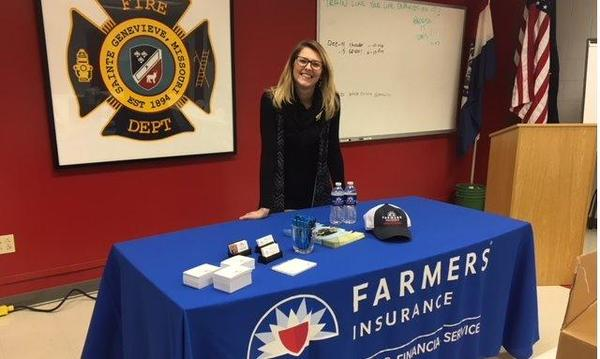 Farmers agent poses with Farmers table and donated firefighters dinner