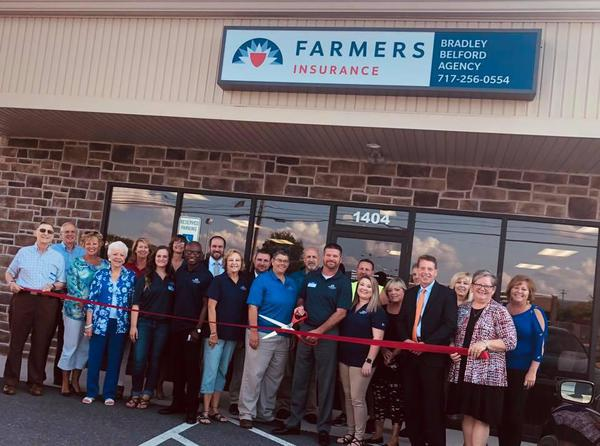 ribbon cutting in front of Farmers office