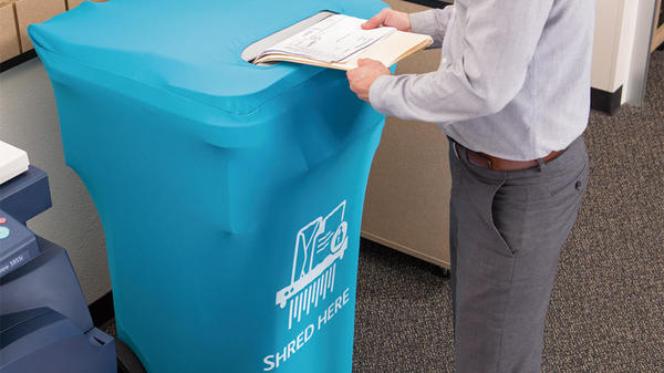 Customer placing documents into covered shredding bin