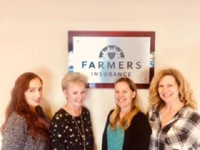 Staff in front of farmers logo