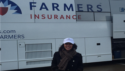 Agent Rani in front of a bus with Farmers logo.
