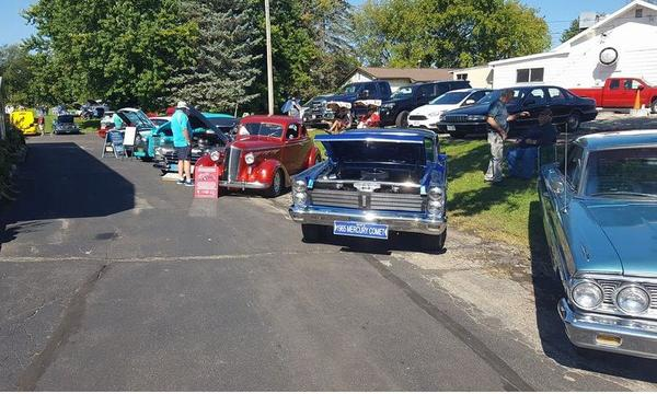 Many cars with their hoods open at a car show