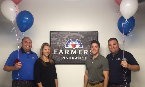 Agent Lukas Perry posing with three staff members holding balloons, standing in front of a framed photo of the Farmers logo.