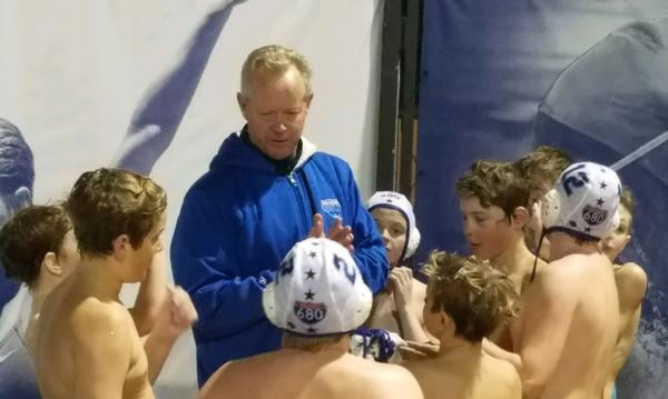 Coach surrounded by young boys water polo team. Some wearing helmets.