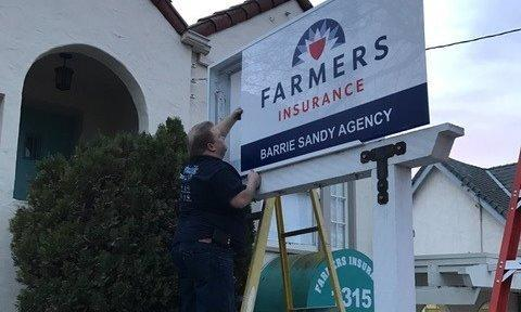 Man putting Farmers Insurance outdoor sign up from a ladder.
