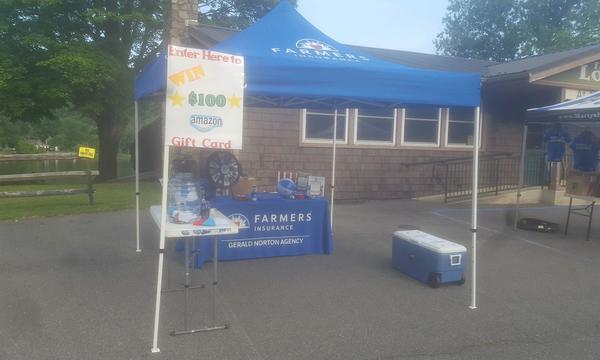A Farmers Insurance promotional table for the Gerald Norton Agency with a raffle sign on it.