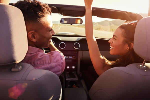 smiling couple in a convertible car with auto insurance from a AAA Agent