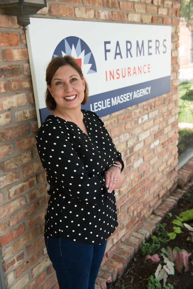 Photo of Agency Owner outside of Farmers Office next to the Farmers sign.