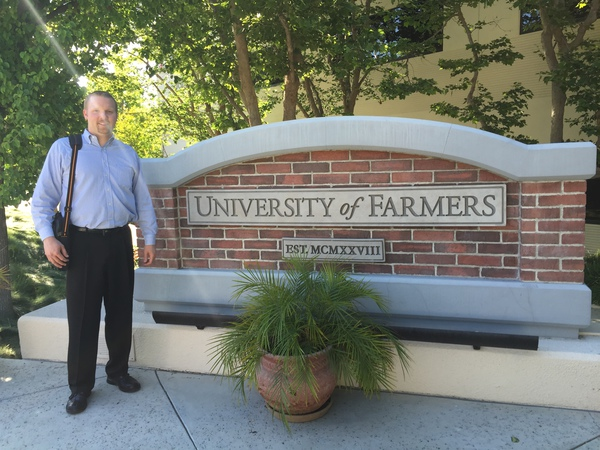 Agent standing in front of Farmers University sign