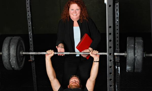 Agent Donna assisting a man on the weight bench.