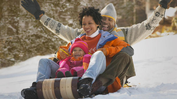 Father mother and child sledding down a snow covered hill