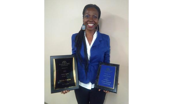 Agent Felicia Traylor standing with two plaques.