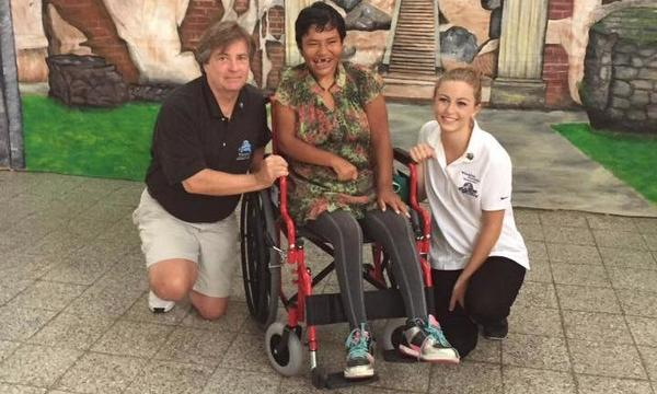 Agent and woman standing with a person in a wheelchair