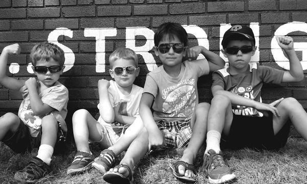 "4 little boys pose against a wall with ""strong"" written on it"