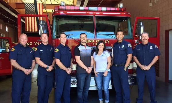 Agent Saed with a woman and 5 firefighters in front of a firetruck