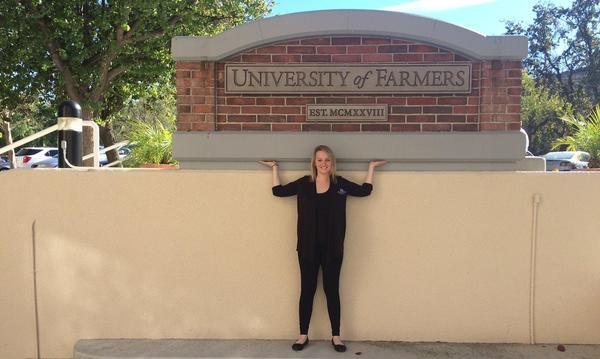 Agent standing beneath the University of Farmers logo