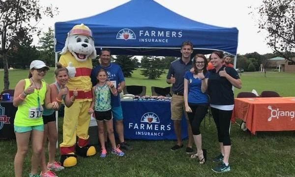 A group of people in front of a Farmers booth pose with a mascot wearing a fireman outfit
