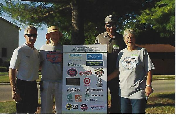Group of adults posing for a photo with a poster board of sponsors on a field of green.