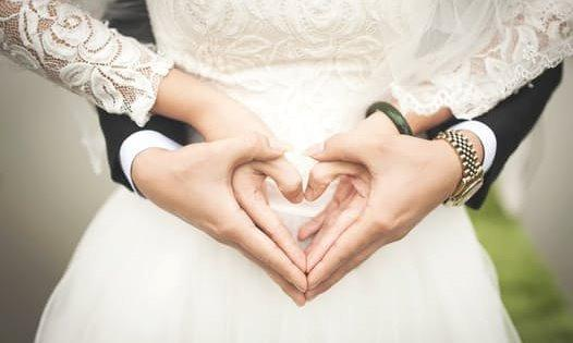 Hands of man and woman in wedding attire making heart shape with hands.