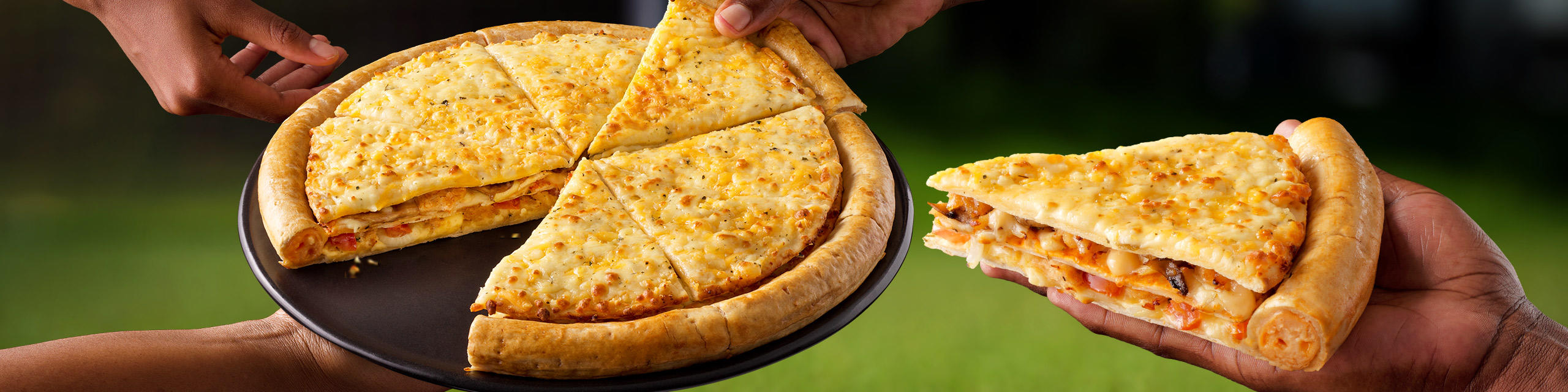 A large Cram-Decker® pizza on a plate with hands grabbing a slice.