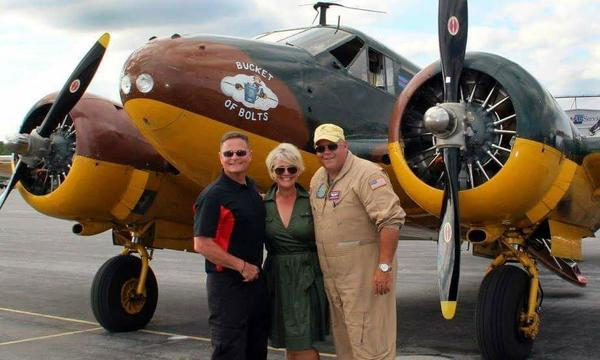 Agent Dawn Gamble with two veterans in front of an old military airplane