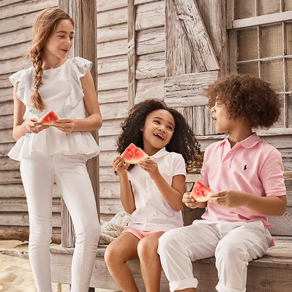 3 kids laughing and enjoying a piece of watermelon