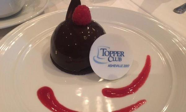 Dessert on a plate with the Topper club logo