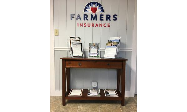Table with Farmers brochures and Farmers logo in the background.