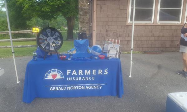 A Farmers Insurance promotional table for the Gerald Norton Agency set up outside.