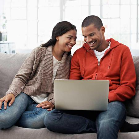 A couple smiles at each other as they apply online from their couch
