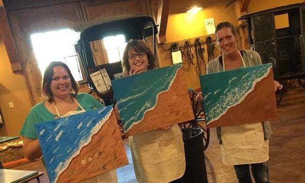 Agent Debra Wilson with two other women holding paintings of ocean waves touching the beach
