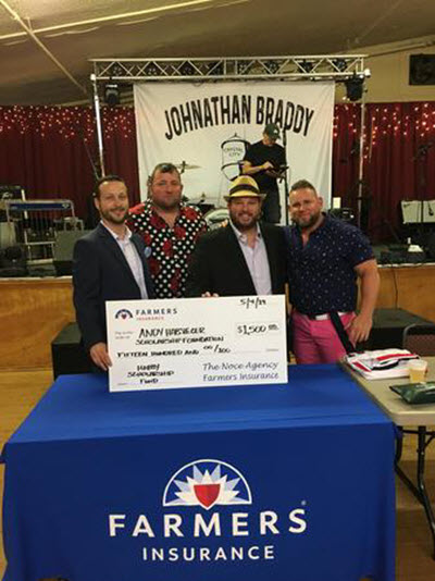 four men holding large check on farmers table