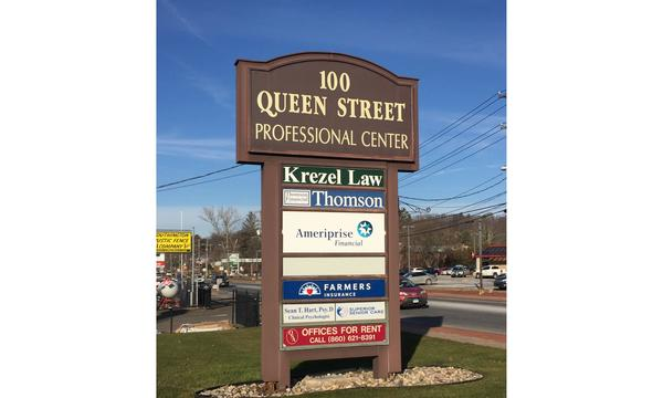 100 Queen Center sign with Farmers logo
