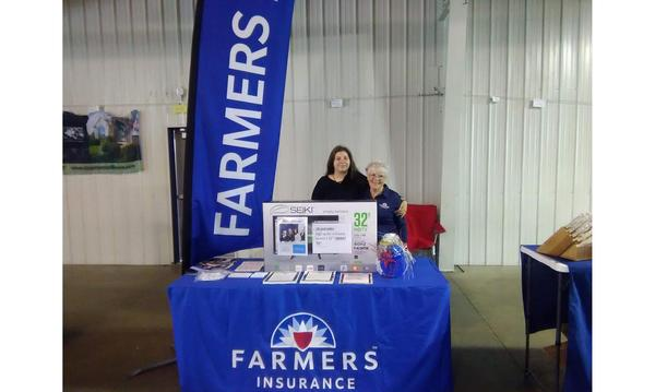 Two women link arms inside at a Farmers booth