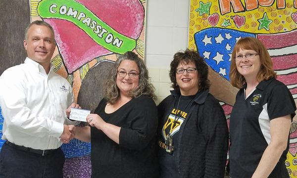 Agent Scott Tarsi presenting a check to three local school teacher.