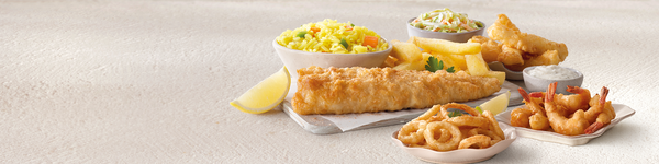 Fried fish, calamari, scampi, rice, coleslaw and ships arranged on a grey table