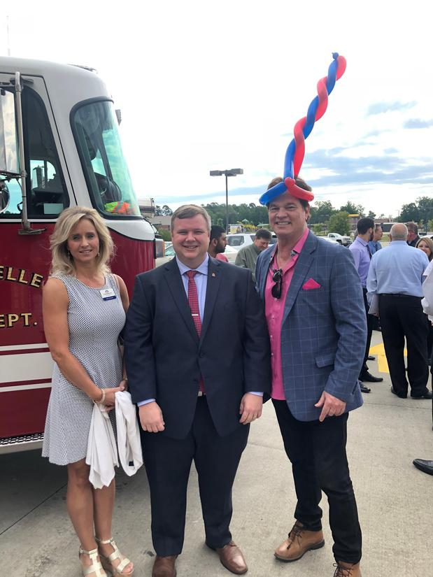 Three people standing in front of a fire truck