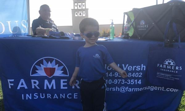 child in front of a Farmers Booth