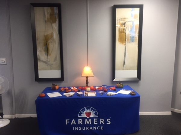 A photo of a table with a Farmers Insurance tablecloth and pamphlets on it.